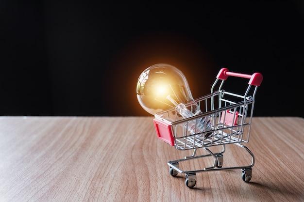 Energiesparlampe mit stapeln von münzen und einkaufswagen zum sparen