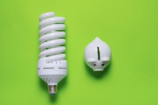 Energiesparlampe und sparschwein auf farbiger oberfläche