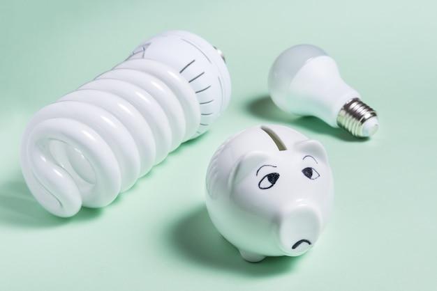 Energiesparlampen und sparschwein auf farbiger oberfläche
