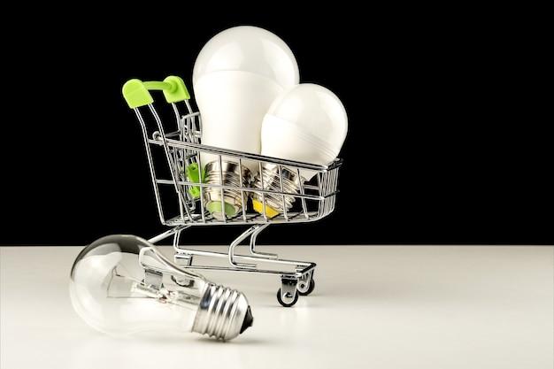 Energiesparlampen werden in einen korb auf rädern gelegt. einfache glühbirne liegt auf dem tisch. konzept der modernen wirtschaftlichen beleuchtung.