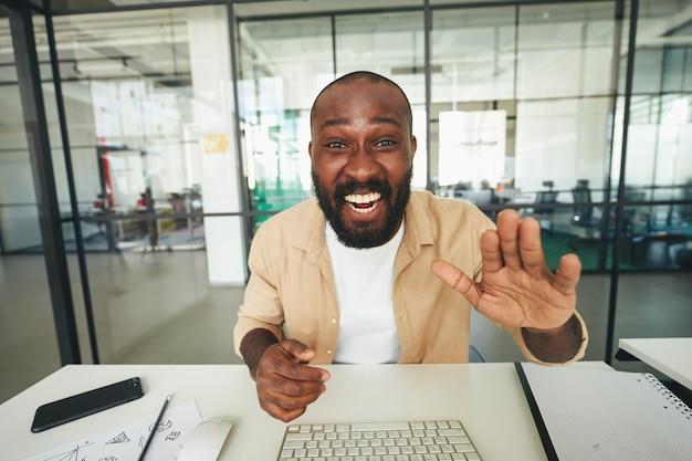 Energischer mann, der in die kamera lächelt und winkt