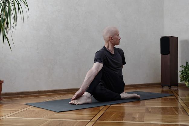 Energischer mann mittleren alters, der yoga-posen macht. gesundes lebensstilkonzept.