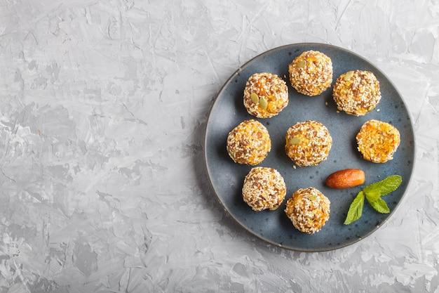 Energy ball kuchen mit getrockneten aprikosen, sesam, leinen, walnüssen und datteln auf grau