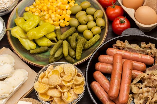 Energy breakfast food set: gurken in dosen, mais, pfeffer in keramikplatte. würstchen in der pfanne. kichererbsenoliven, tomaten.