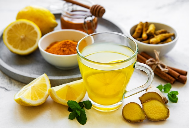 Energy tonic drink mit kurkuma, ingwer, zitrone und honig auf weißem marmor