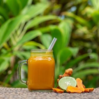 Energy tonic drink mit kurkuma, ingwer, zitrone und honig im glasbecher, naturhintergrund, nahaufnahme