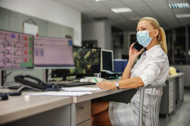 Engagierte fleißige blonde chefin im anzug mit gesichtsmaske beim sitzen im kontrollraum im heizwerk und bei wichtigen telefongesprächen während des ausbruchs des koronavirus.