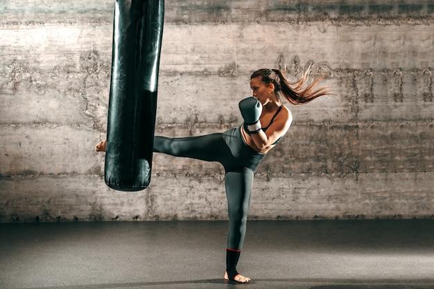 Engagierte starke brünette mit pferdeschwanz, in sportbekleidung, nacktem fuß und mit boxhandschuhen, die im fitnessstudio gegen den sack treten.