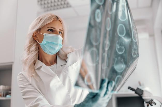 Engagierter arzt, der eine röntgenaufnahme des gehirns des patienten hält und es betrachtet.