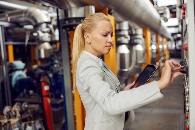 Engagierter blonder weiblicher aufseher im anzug, der tablette hält und auf armaturenbrett im heizwerk einstellt.