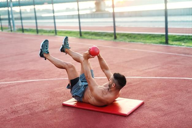 Engagierter hemdloser muskulöser kaukasischer mann mit kurzem haarschnitt, der auf der matte sitzt und übungen mit kettlebell macht. outdoor-fitness-konzept.