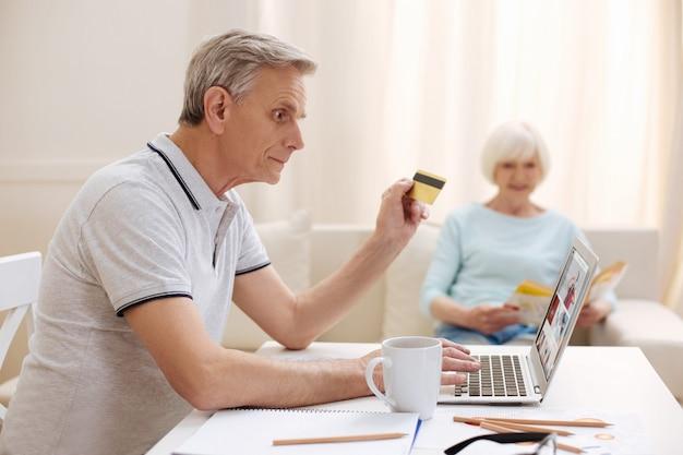 Engagierter intelligenter älterer herr, der nach einem geeigneten artikel sucht und ihn in einem online-shop kauft, während er mit seiner kreditkarte bezahlt
