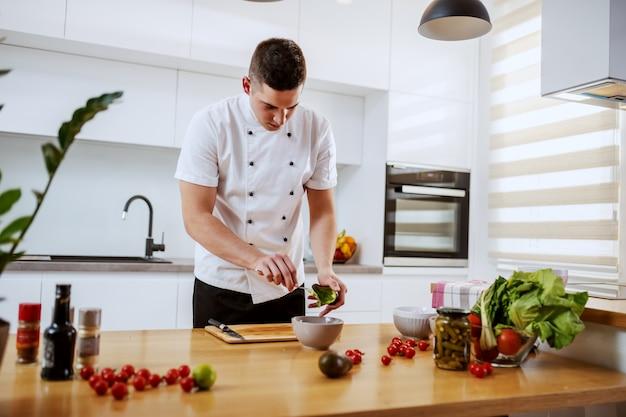 Engagierter kaukasischer koch in uniform, die avocado für mahlzeit vorbereitet