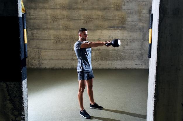 Engagierter muskulöser mann in sportbekleidung, der übungen mit kettlebell macht, während er im cross-fit-fitnessstudio steht.