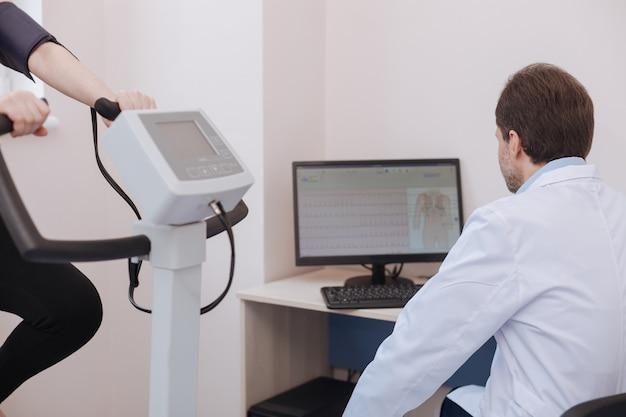 Engagierter professioneller junger kardiologe, der mit seinem computer die körperliche leistungsfähigkeit der patienten beobachtet und schlussfolgerungen zieht