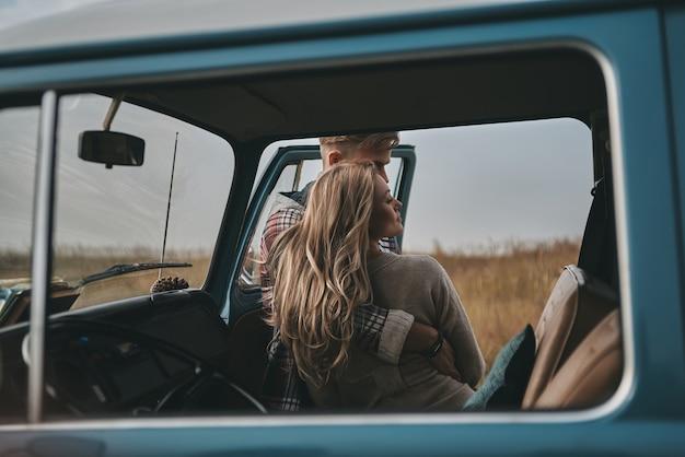 Enge beziehung ... schönes junges paar, das umarmt, während es draußen in der nähe des minivans im retro-stil steht