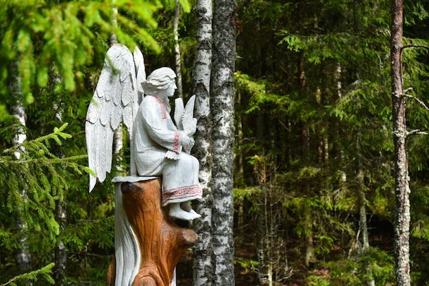 Engel mit einer taube auf einem baum im wald