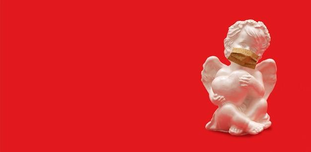 Engel mit herz in der medizinischen maske auf rotem hintergrund - valentinstag-pandemiekonzept-bannerformat Premium Fotos