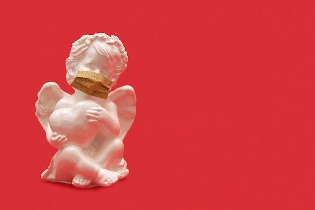 Engel mit herz in der medizinischen maske auf rotem hintergrund - valentinstag-pandemiekonzept Premium Fotos