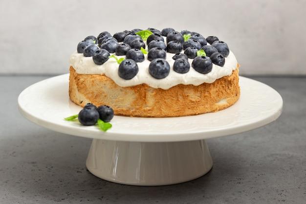Engelsnahrungsmittelkuchen mit schlagsahne und blaubeeren.