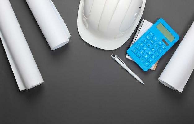 Engineering bau sicherheitshelm, blaupausen, projektplan und taschenrechner auf grau