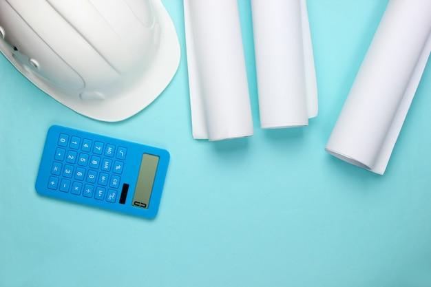 Engineering bau sicherheitshelm, blaupausen und taschenrechner auf blau. berechnung der kosten für den bau eines hauses. flach liegen