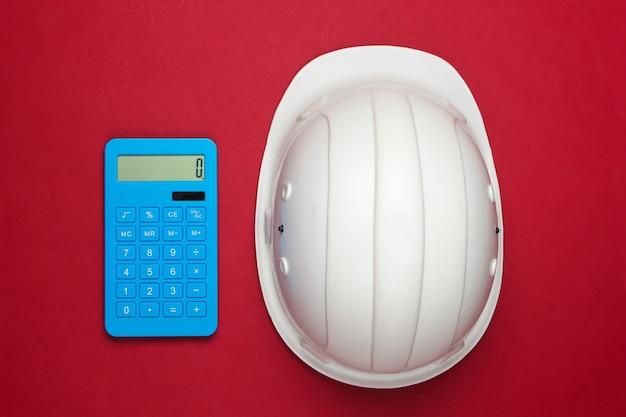 Engineering bau sicherheitshelm und taschenrechner auf rot. berechnung der kosten für die reparatur oder den bau eines hauses. flach liegen