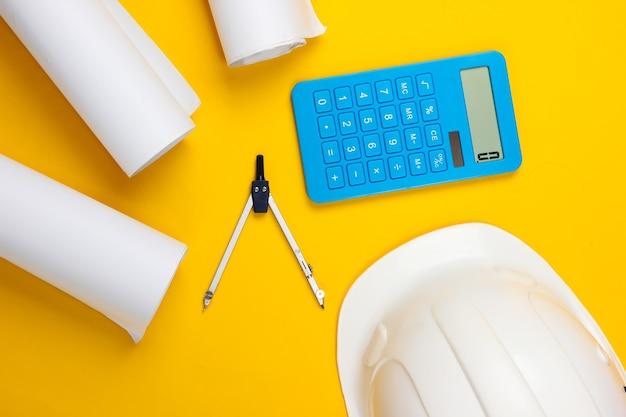 Engineering bau sicherheitshelm, zeichenrollen, kompass und taschenrechner auf gelb. berechnung der kosten für den bau eines hauses. flach liegen