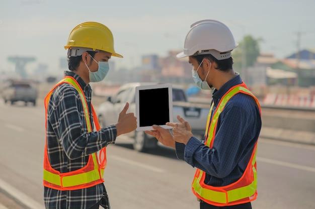 Engineering holding tablet arbeit am straßenbau, construction engineering verwenden weiße tablet-anwendung arbeiten gebäude estate architektur