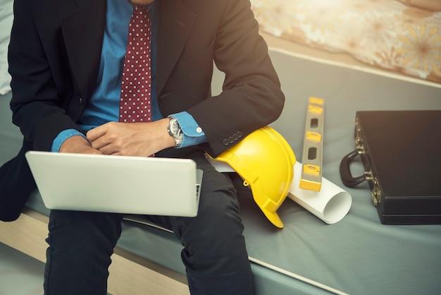 Engineering-konzept. geschäftsmann, der mit laptop im raum mit sturzhelm, geschäftstasche und arbeitet