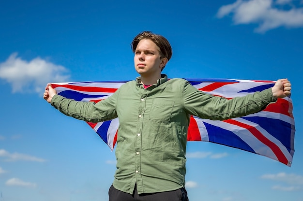 England-flagge, junger mann, der eine große england-flagge gegen den himmel hält