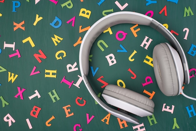 Englisch hören podcast-konzept lernen. oben über der draufsicht foto von ohrhörern, die auf greenboard mit bunten buchstaben isoliert sind