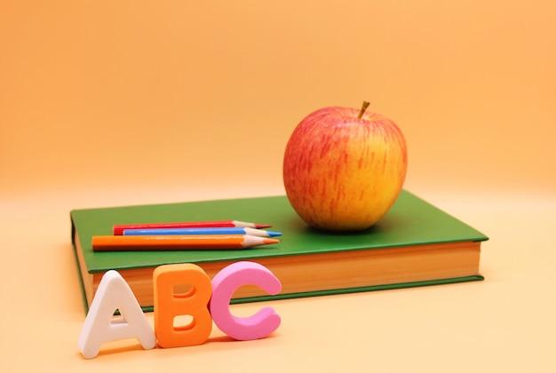 Englische abc-alphabetbuchstaben nahe bei buch und apfel.