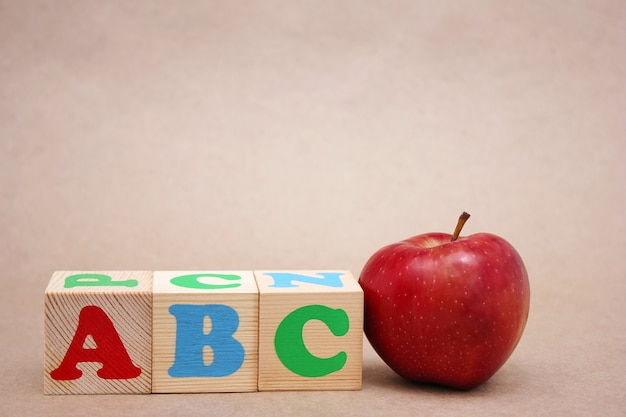Englische abc-alphabetbuchstaben neben einem roten apfel