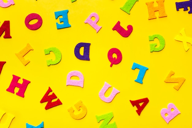 Englische alphabetbuchstaben auf einem gelben hintergrundmuster.