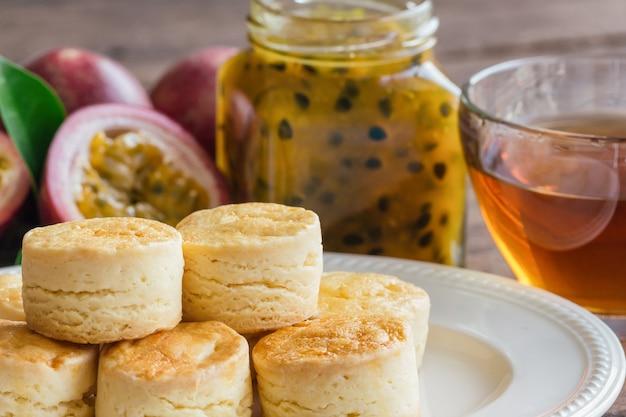 Englische traditionelle selbst gemachte einfache scones dienten mit selbst gemachter maracujamarmelade und -tee.