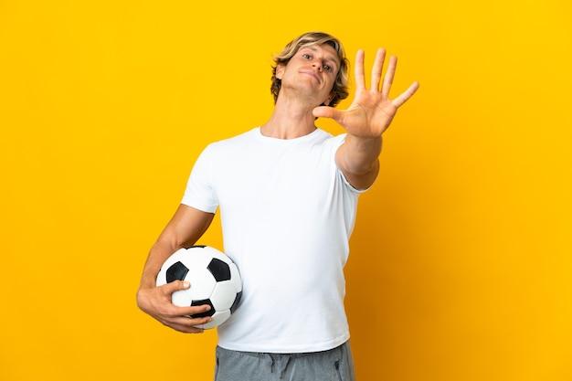 Englischer fußballspieler auf isoliertem gelb, das fünf mit den fingern zählt