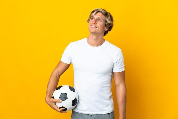 Englischer fußballspieler über isoliertem gelbem hintergrund, der eine idee beim nachschlagen denkt