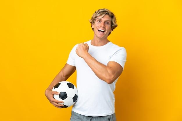Englischer fußballspieler über isoliertem gelbem hintergrund, der einen sieg feiert