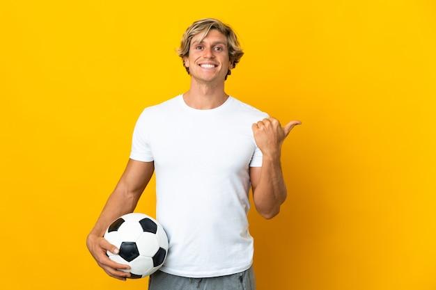 Englischer fußballspieler über isoliertem gelbem hintergrund, der zur seite zeigt, um ein produkt zu präsentieren