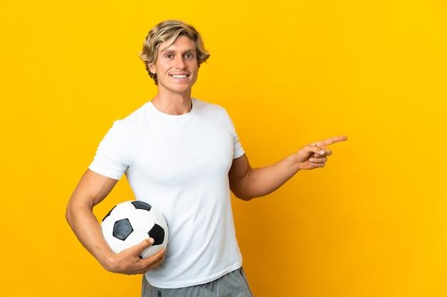 Englischer fußballspieler über lokalisiertem gelbem hintergrund, der finger zur seite zeigt