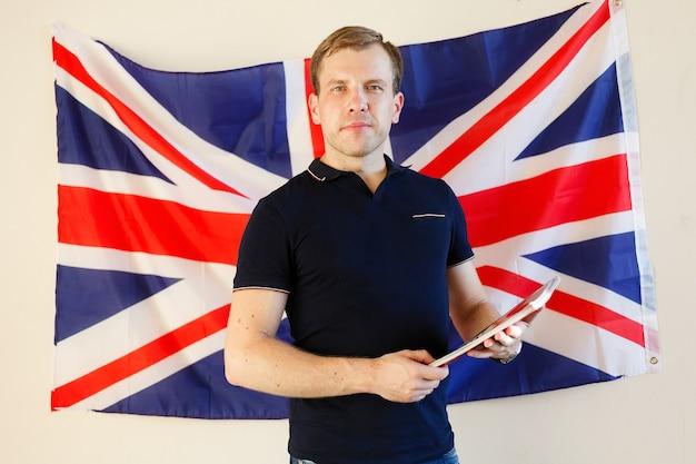 Englischer männlicher student mit der britischen flagge im hintergrund englisch, lernen, studieren.