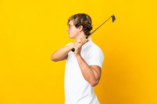 Englischer mann auf isoliertem weiß, das golf spielt