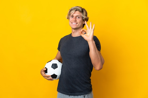 Englischer mann isolierte gelben hintergrund mit fußball und machte ok-zeichen