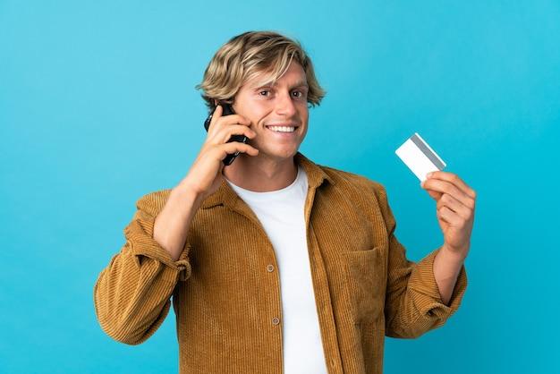 Englischer mann über isoliertem blauem hintergrund, der ein gespräch mit dem mobiltelefon hält und eine kreditkarte hält