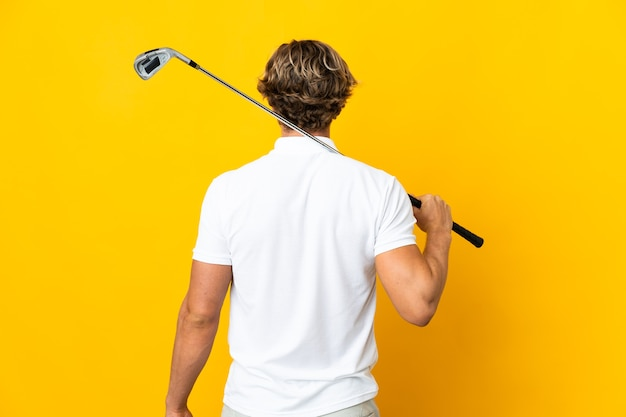 Englischer mann über isoliertem weißem hintergrund, der golf und in der hinteren position spielt