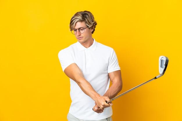 Englischer mann über isolierter weißer wand, die golf spielt