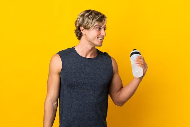 Englischer mann über lokalisiertem gelbem hintergrund mit sportwasserflasche