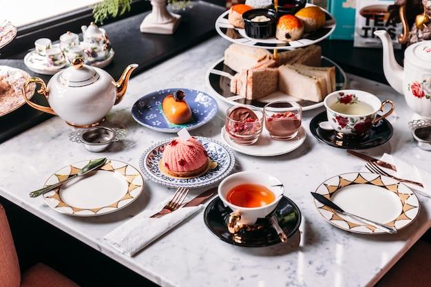 Englischer nachmittagsteesatz mit heißem tee, gebäck, scones, sandwiches und mini-pies.