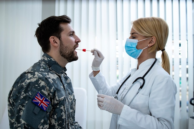 Englischer soldat in uniform beim pcr-test in der arztpraxis während der covid19-virus-epidemie